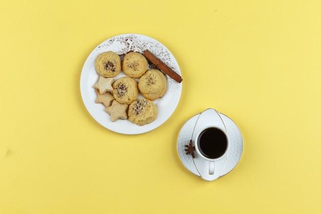 Печенье и чашка кофе на желтом фоне