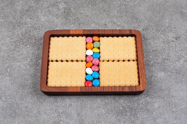 木の板にビスケットとカラフルなキャンディー