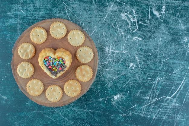 青い背景の上のボード上のハート型のケーキの周りのビスケット。高品質の写真