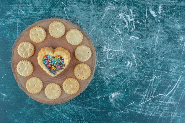 Biscuits around a heart shaped cake on a board on blue background. high quality photo