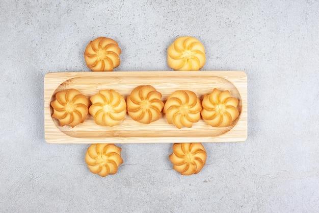 Biscotti su e intorno a una tavola di legno su sfondo di marmo. foto di alta qualità