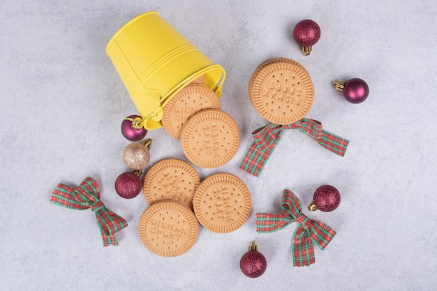 Biscuits in bucket decorated with ribbon and christmas balls on white table. high quality photo