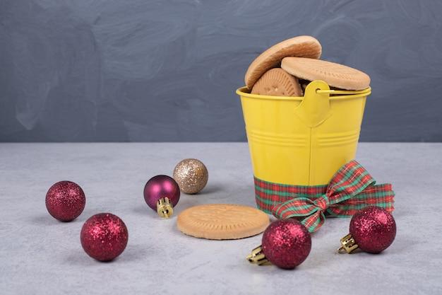 Biscotti nel secchio decorato con nastro e palle di natale sul tavolo bianco. foto di alta qualità