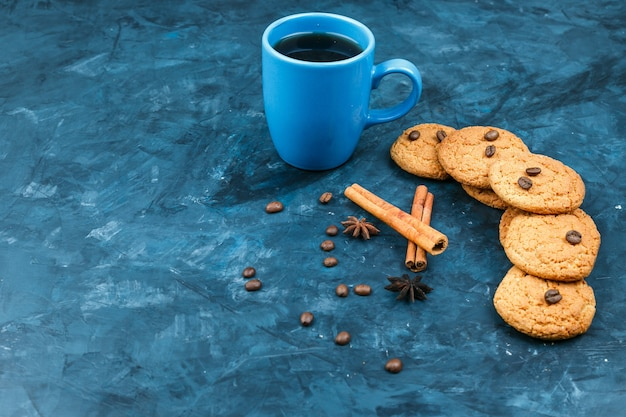 Biscotti e tazza di caffè su uno sfondo blu scuro
