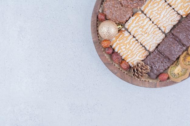 Biscotti, frutta secca e palle di natale su tavola di legno.