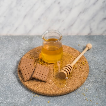 Biscuits and honey pot with wooden dipper on cork coaster over the granite backdrop