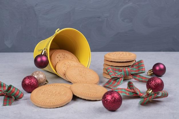 양동이에 비스킷은 흰색 테이블에 리본과 크리스마스 볼 장식. 고품질 사진