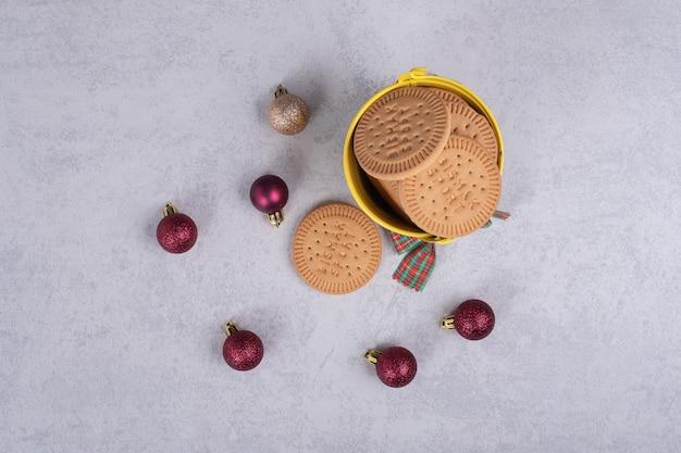 양동이에 비스킷 흰색 테이블에 밧줄과 크리스마스 볼 장식. 고품질 사진