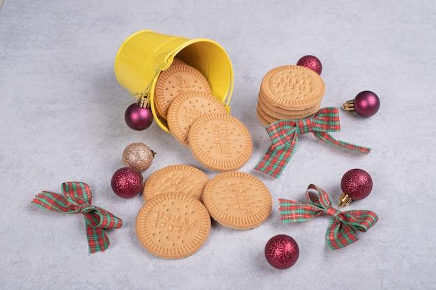 Печенье в ведре, украшенном веревкой и елочными шарами на белом столе.