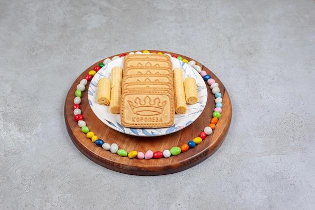 비스킷은 접시에 줄 지어 대리석 배경에 나무 보드에 사탕으로 둘러싸여 있습니다. 고품질 사진