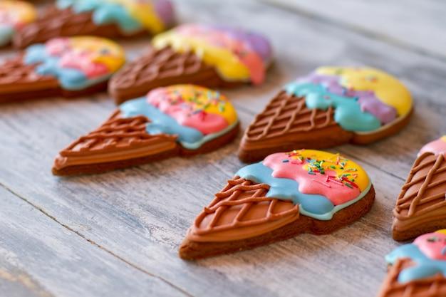 회색 나무 표면에 비스킷입니다. 밝은 색의 디저트. 맛있는 아이스크림 콘 쿠키. 아이들을 위한 맛있는 놀라움.