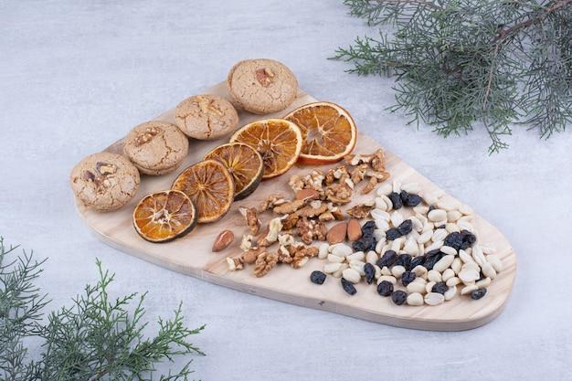 木の板にビスケット、オレンジ、さまざまなナッツ。