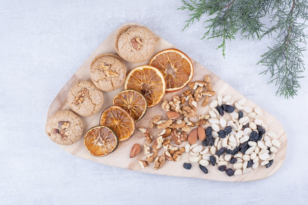 Biscuits, oranges and various nuts on wooden board.