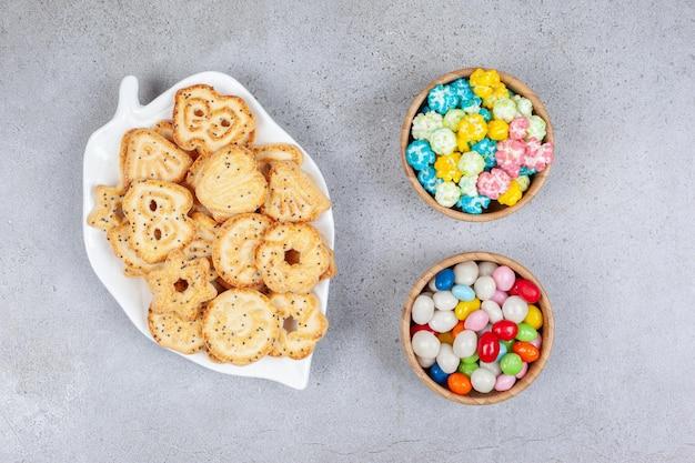 Biscotti su un piatto decorato accanto a ciotole di caramelle sulla superficie di marmo.