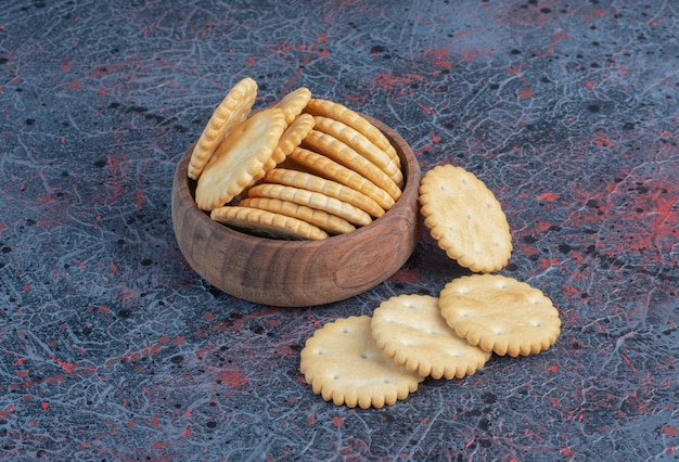 Biscuits in a small bowl on abstract table.