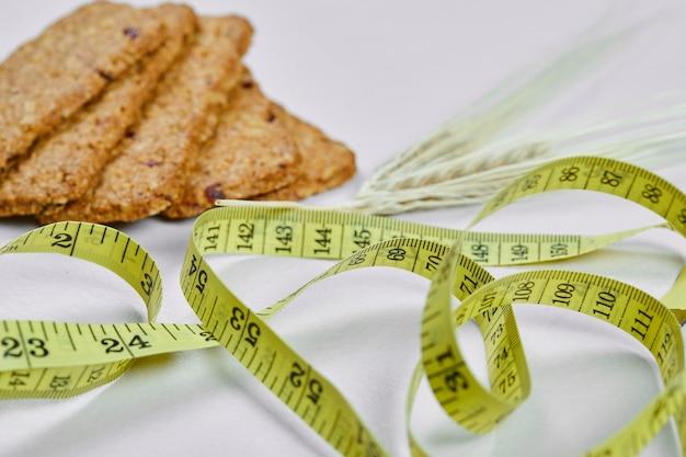 Biscotti e metro a nastro su uno sfondo bianco. foto di alta qualità