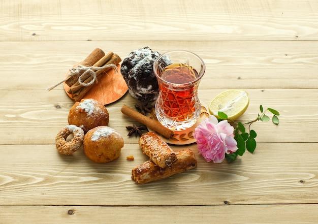 Печенье с бокалом чая, палочки корицы, цветок, лимон, гвоздики на деревянной поверхности, высокий угол обзора.