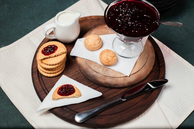 Biscuits with red raspberry jam on a wooden board