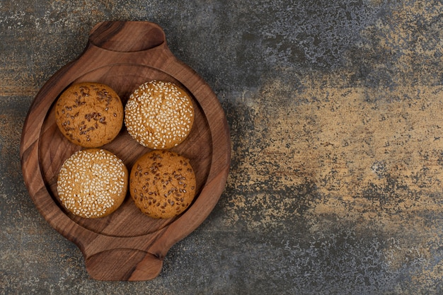 Biscuits with sesame seeds and chocolate pieces on wooden board.