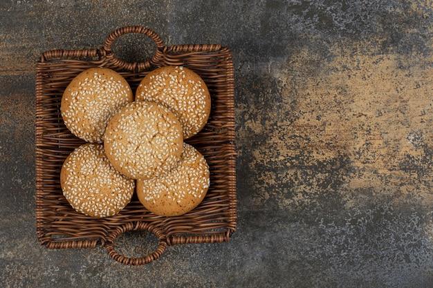 Печенье с кунжутом в деревянной корзине.