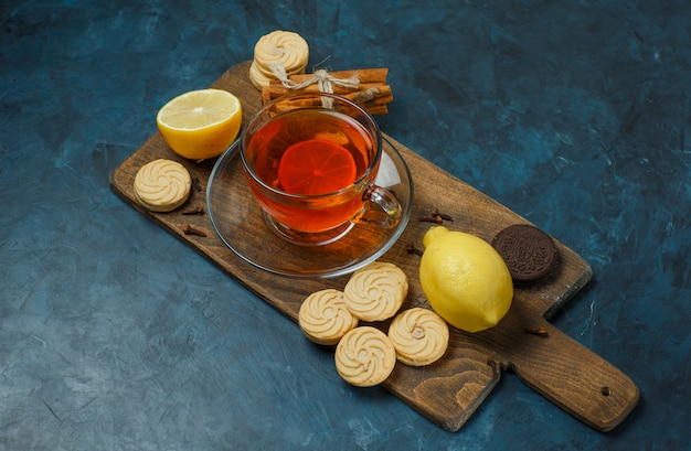 Biscuits with spices, tea, lemon on dark blue and cutting board