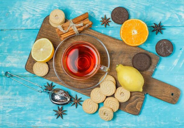 Biscuits with spices, tea, lemon, orange, strainer on blue and cutting board
