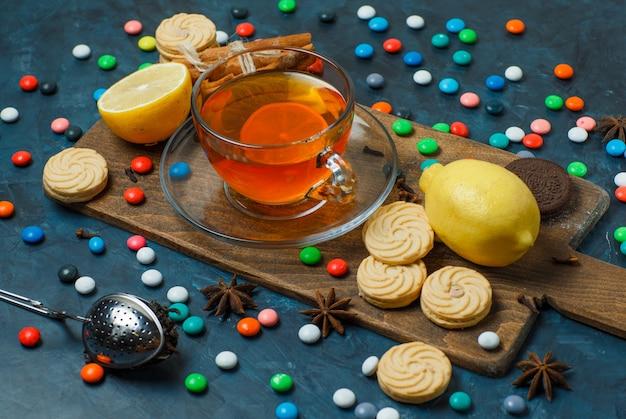 Печенье с конфетами, специями, чаем, лимоном под высоким углом зрения на штукатурке и разделочной доске