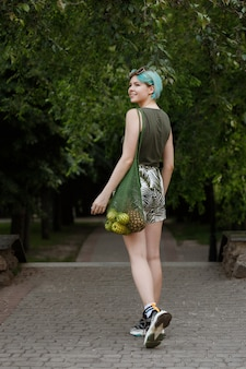 Bisexual girl walks through the park with a bag of fruit. healthy lifestyle