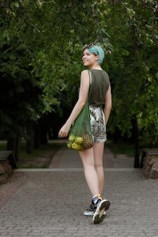 両性愛の女の子が果物の袋を持って公園を歩きます。健康的な生活様式