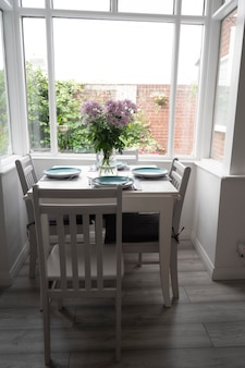 Bishop, auckland, u.k. 27 july, 2021. beautiful dinning room withwhite table, chair and lovely flower bouquet