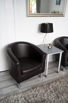 Bishop, auckland, u.k. 27 july, 2021. living room with two clasic black leather armchair and table with a lamp. interior design, hotel furniture.