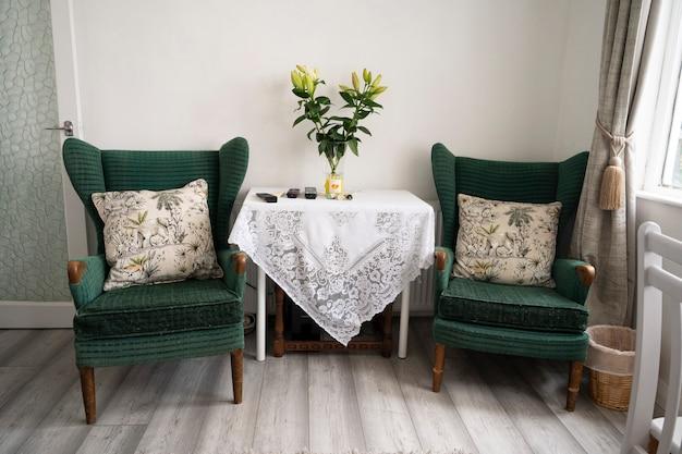 ビショップ、オークランド、イギリス2021年7月27日。2つの古い、ヴィンテージの緑のベルベットのアームチェアと花のテーブルのあるリビングルーム。インテリアデザイン、ホテルの家具。