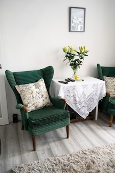 Bishop, auckland, u.k. 27 july, 2021. living room with two old, vintage green velvet armchair and table with flowers. interior design, hotel furniture.