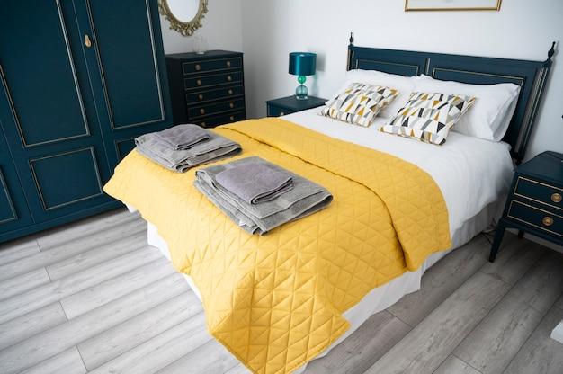 ビショップ、オークランド、イギリス2021年7月27日。ホテルの部屋にスタイリッシュなダブルベッド。ベッドにタオルが付いた灰色のベッドルーム、すぐにチェックインできます。屋内の家のデザイン
