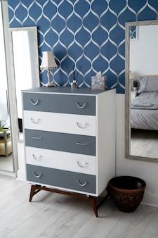 ビショップ、オークランド、イギリス2021年7月27日。灰色の壁、鏡とランプのあるワードローブのあるスタイリッシュなホテルの部屋。インテリアデザインの家具要素。
