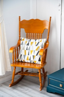 Bishop, auckland, u.k. 27 july, 2021. stylish old wooden rocking chair with colorful moder cusion, living room furniture.