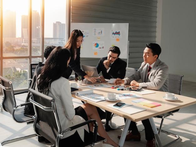 多民族のパートナーと話し合うオフィスで文書を説明する立っているビジネスの女性