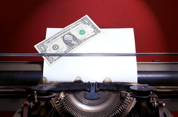Руководство bisnesman, доллар на бумаге на старинной ручной пишущей машинке.