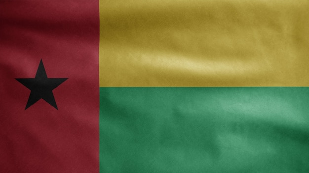 Bissau guinean flag waving in the wind. close up of guinea bisau banner blowing, soft and smooth silk. cloth fabric texture ensign background.