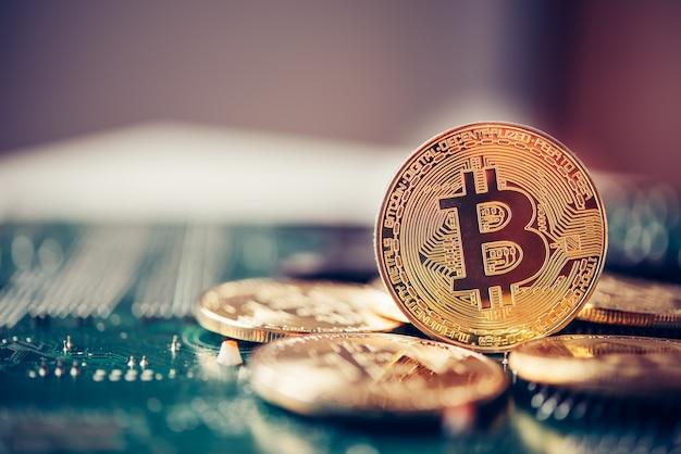 電子機器に置かれたビットコイン。金融の進化的概念