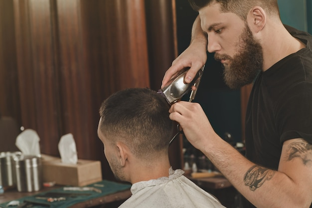 A bit more here. bearded barber finishing his work on hairstyling