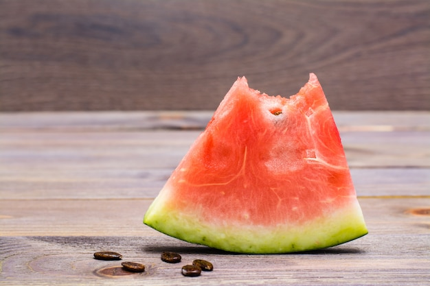 A bit of watermelon and watermelon seeds on woodtable