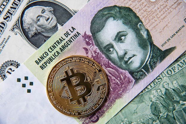 Bitcoin against argentinian peso and american dollar, close-up image. conceptual image of digital crypto currency against world traditional currency