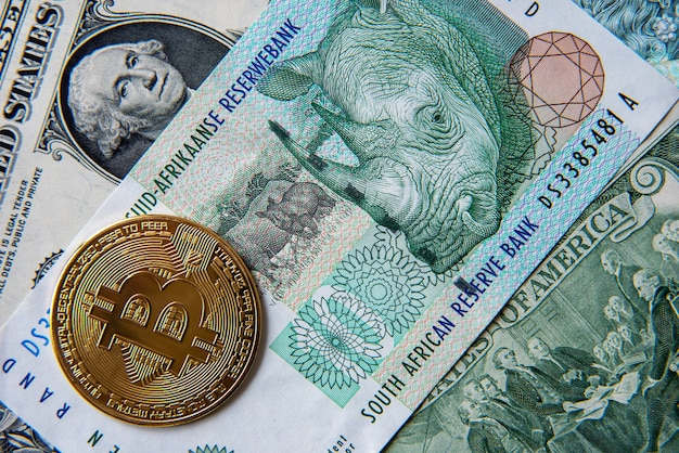 Bitcoin against south african rand and american dollar, close-up image. conceptual image of digital crypto currency against world traditional currency