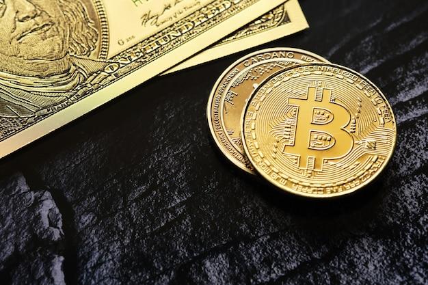 100달러 지폐와 복사 공간이 있는 비트코인 및 카르다노 암호화폐