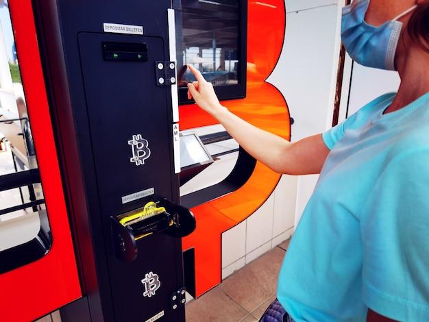 비트코인 atm 기계. 의료용 마스크를 쓴 여성이 비트코인을 구매합니다. 암호화폐. 돈 기술