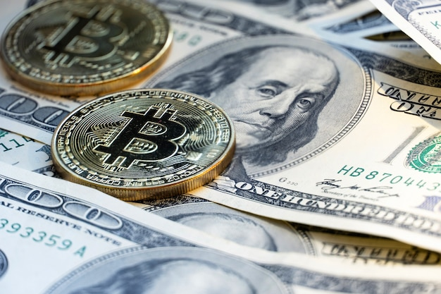 Bitcoin on the background of 100 dollar bills.