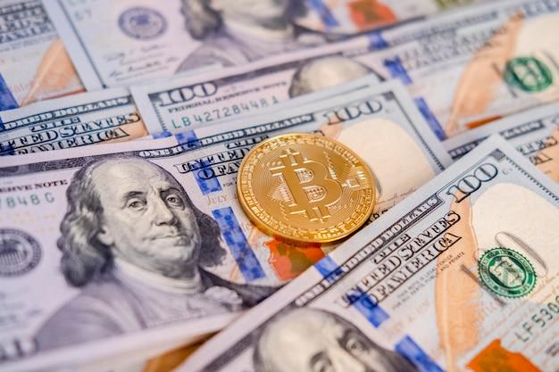 Золотая монетка bitcoin на долларах сша закрывает вверх. btc. биткойн наличными.