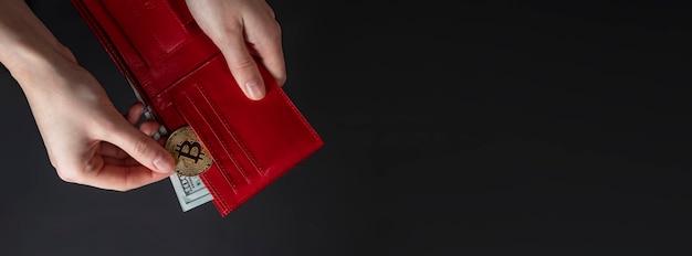 黒の背景に赤い財布のビットコインコインと米ドル、クローズアップ。テキスト用のコピースペース付きバナー