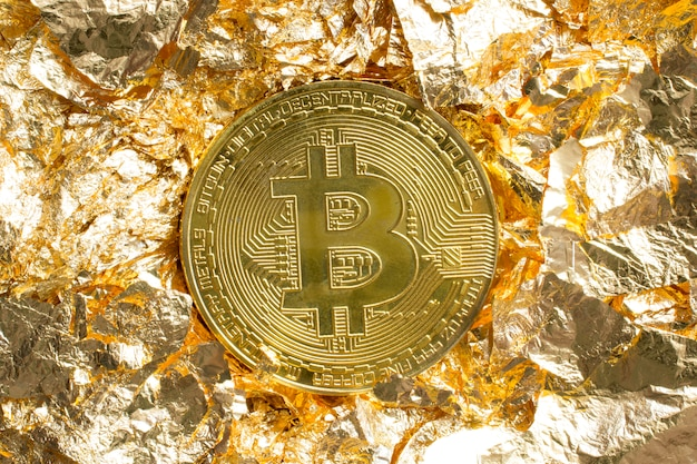 Bitcoin coin on golden foil pieces around decorative background